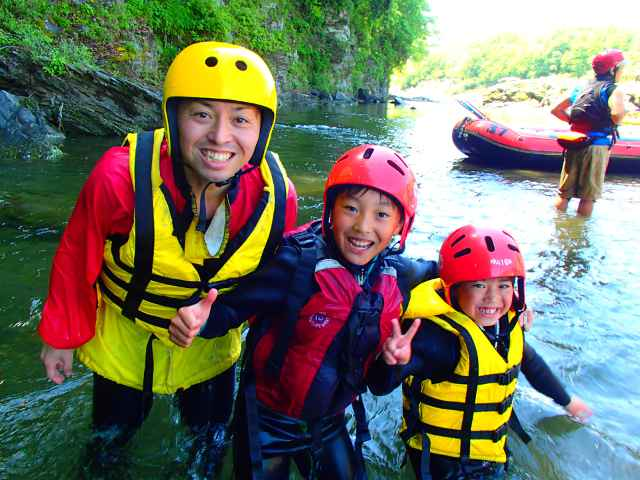 Kids have a big smile in the river.